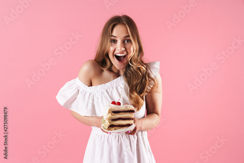 Obraz Image of attractive surprised woman wearing white dress smiling at camera and holding piece of cake with candle - fototapety do salonu