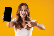 Image Closeup Of Young Caucasian Woman Wearing Basic T-shirt Rejoicing While Pointing Finger At Cellphone