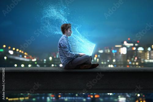Obraz Mann sitzt am Notebook vor nächtlicher Stadt - fototapety do salonu