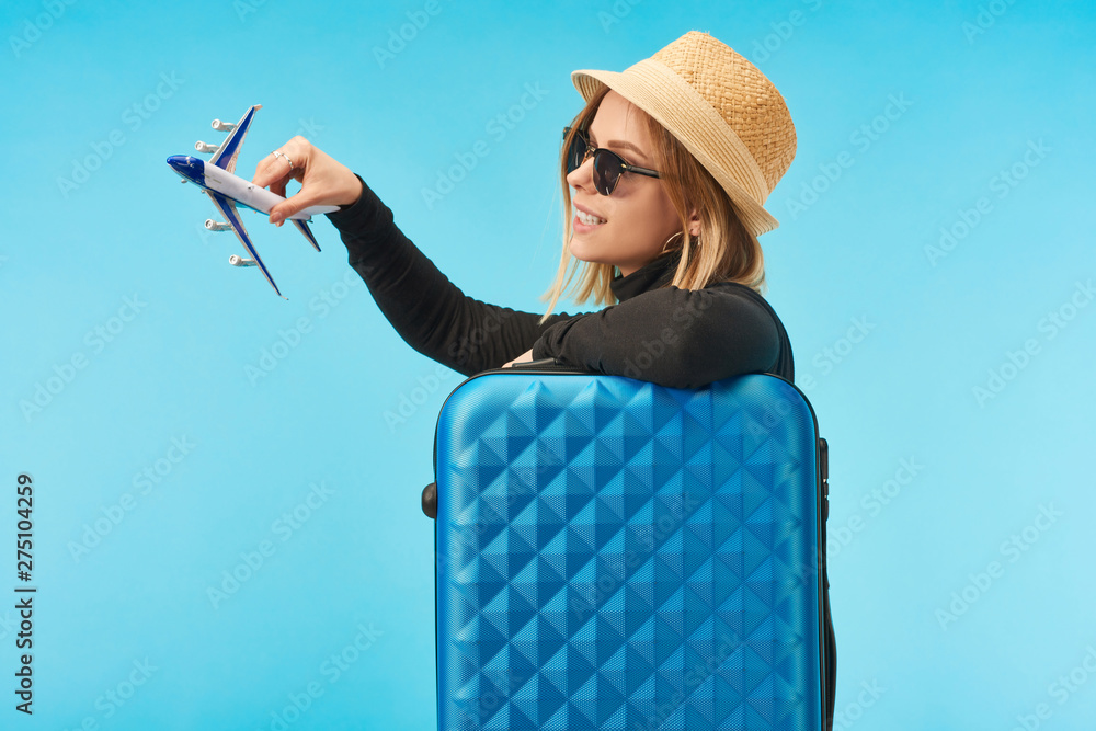 Fototapety, obrazy: blonde happy girl in sunglasses and straw hat plating with toy plane near blue travel bag isolated on blue