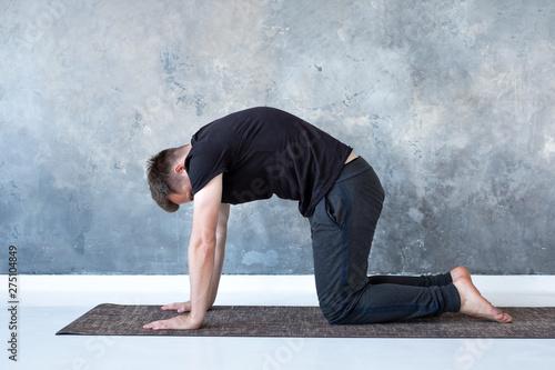 Stampa su Tela  Young yogi men practices yoga asana bitilasana or cat cow pose
