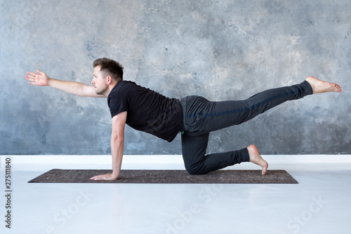 Young caucasian men practices yoga asana chakravakasana Wallpaper Mural
