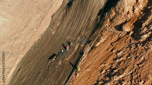 Fototapeta Workers strengthen the slope of the mountain with metal mesh preventing rockfall and landslide on the road, above view