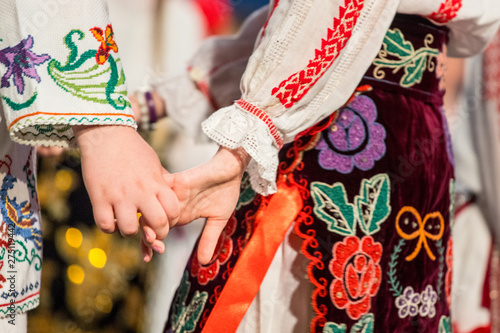 Foto Close up of hands of young Romanian dancers perform a folk dance in traditional folkloric costume