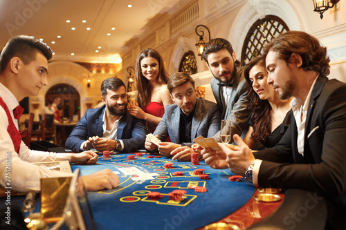 A group of people playing gambling in a casino Fototapeta