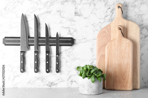 Valokuvatapetti Magnetic holder with set of knives on marble wall in kitchen