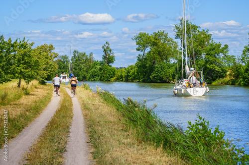 Couple cycling along a canal with boats Slika na platnu