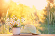 Leinwandbild Motiv beautiful daisies in white cup, book, braided hat in summer garden. Rural landscape natural background with  Chamomile flowers in sunlight. Summer time. copy space