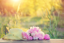 Pink Peonies And Summer Hat Outdoors. Beautiful Peony And Braided Hat In Summer Garden. Rural Landscape Natural Background With  Pink Flowers In Sunlight. Summer Time.  Copy Space