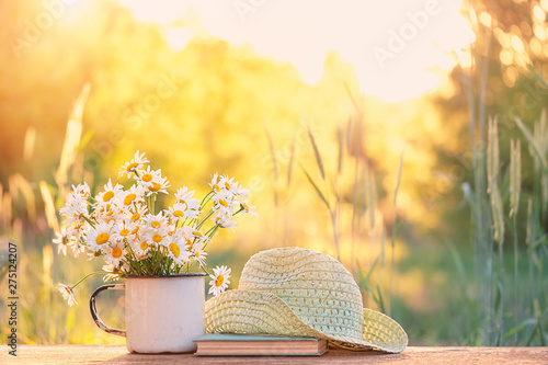 Leinwand Poster beautiful daisies in white cup, book, braided hat in summer garden