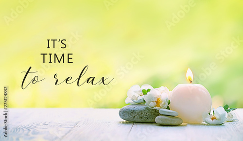 it's time to relax. beautiful scene with candle, flowers and stones. romantic still life. Relax still life with zen pebble stones, candle. spa wellness scene, soul equanimity calmnes concept
