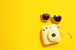 canvas print picture - Sunglasses and camera on color background, top view with space for text. Beach accessories