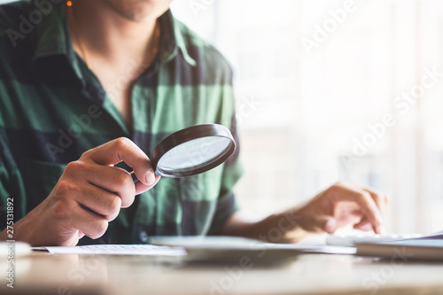 Man looking through a magnifying glass to documents Wallpaper Mural