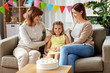 family, generation and celebration concept - smiling mother, daughter and grandmother at birthday party