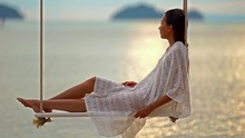 Beautiful Woman Relaxing On Swing Hanging Over The Ocean, Eye Level Shot, Real Time, Blurred Background