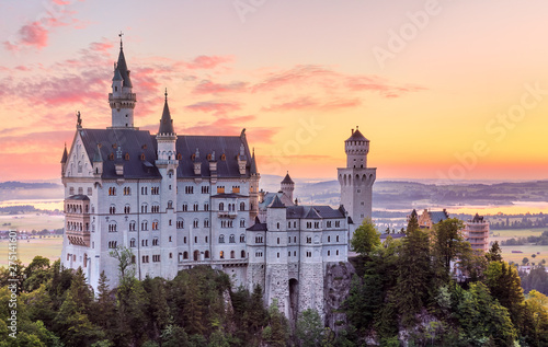 Foto auf Leinwand Aubergine lila Bavaria, Germany. Fairytale Neuschwanstein Castle in Bavarian Alps mountains. Picturesque view at valley with lake and sunrise sky with clouds. Famous landmark and touristic travel destination.