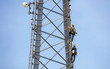 canvas print picture - Telecom maintenance. Two repair men climbing on tower against blue sky background