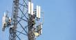 Leinwandbild Motiv Telecom maintenance. Man climber on tower against blue sky background