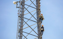Telecom Maintenance. Two Repair Men Climbing On Tower Against Blue Sky Background