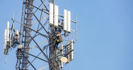 Telecom maintenance. Man climber on tower against blue sky background
