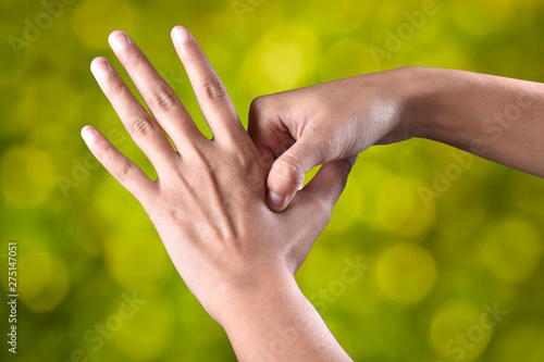 Photo female hands make acupressure on the arm over beautiful green background