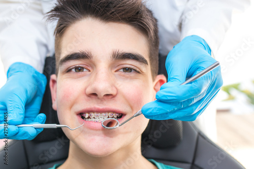 Carta da parati  dentist with tools in the young man's mouth with orthodontics