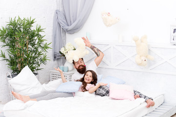 Obraz na płótnie Canvas Having fun pajamas party. Slumber party. Happy fatherhood. Ending of crazy evening. Dad and girl relaxing bedroom. Pajamas style. Father bearded man funny hairstyle ponytails and daughter in pajamas