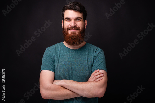 Canvastavla  Portrait of smiling young man with crossed arms looking at the camera