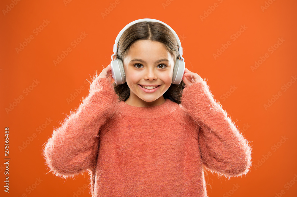 Fototapety, obrazy: Perfect sound stereo headphones. Girl cute little child wear headphones listen music. Kid listen music orange background. Recommended music based on initial interest. Music produces pleasure
