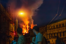 Fire In Night, Burning Building Roof And Blurred People On Foreground Watching Accident In City Street