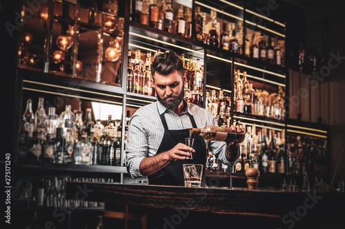 Photo Serious barman is prepairing drinks for customers at posh bar.