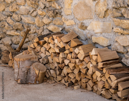 Poster Pays d Europe Chopped wood and axe stacked against the stone wall of a rustic farmhouse
