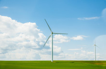 Wide Image Of Two New Windmills In Green Fresh Fields In The Spring With Large Cumulus Clouds In Background Concept Of Environmental Protection And Green Pure Energy From The Wind