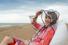 A Woman In A Transparent Raincoat Relaxes On An Inflatable Chair By The Sea, The Ocean During A Light Rain.
