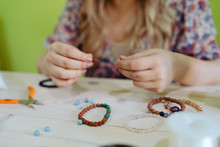 Young Woman Making Crystal Jewelery Necklace And Bracelet At Home Manually