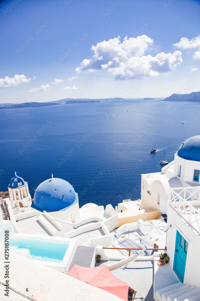 Fototapeta traditional blue doomed churches and white houses in Santorini, Cyclades islands Greece - amazing travel destination