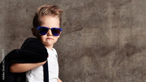 Fotografía  Cute stylish boy sitting on chair near concrete wall