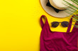 Leinwandbild Motiv Stylish sunglasses with female swimsuit and hat on color background