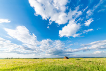 Freshly Bales Of Hay On Autumn Field With White Clouds In Blue Sky