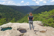 Young Woman Enjoys The View Of The New River Gorge Bridge From The End Of The Long Point Trail In West Virginia.