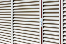Entrance Door In The Wall Of Storehouse. Metal Louver For Ventilation