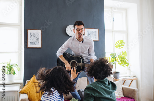 Foto op Canvas Op straat A group of young friends with guitar indoors at home, house sharing concept.