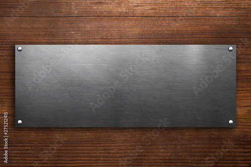 Metal signboard on wooden background