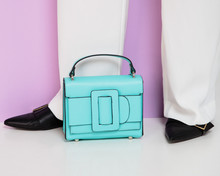Blue Leather Handbag Near The Legs Of The Model In White Pants And Black Shoes
