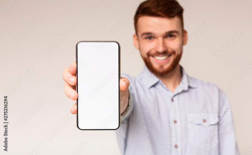 Fototapeta Young guy showing his phone with blank space on camera