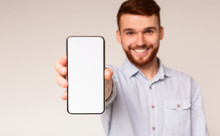 Young Guy Showing His Phone With Blank Space On Camera