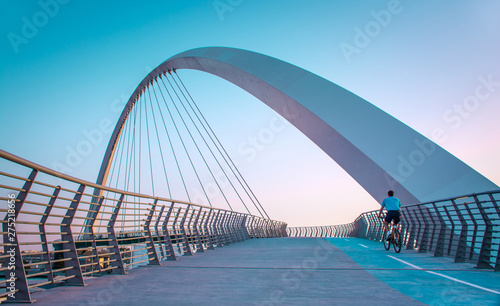 Foto op Aluminium Bruggen Young man riding bicycle through Dubai water canal bridge
