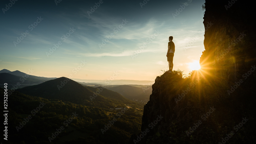 Fototapety, obrazy:  Silhouette of the person on the high rock at sunset. Satisfy hiker enjoy view. Tall man on rocky cliff watching down to landscape. Vivid and strong vignetting effect.