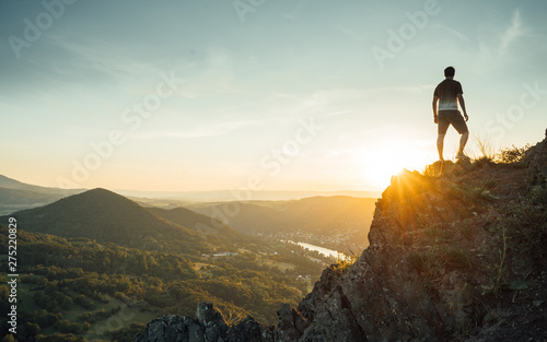 Canvas Prints Beige Silhouette of the person on the high rock at sunset. Satisfy hiker enjoy view. Tall man on rocky cliff watching down to landscape. Vivid and strong vignetting effect.