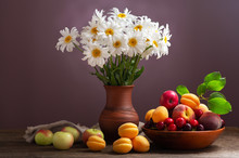 Still Life With Bouquet Of Daisy Flowers In A Jar And Fresh Fruits